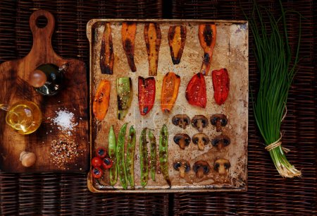 Photo for Baked vegetables and mushrooms beautifully arranged on a baking sheet, next to the table is a bottle with oil and balsamic vinegar, chives  composition imparts freshness - Royalty Free Image