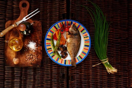 Cook the fish served with vegetables on a bright plate, next to the table lies a dark bunch of fresh onions on a cutting left dock is soli pepper olive oil and soy sauce