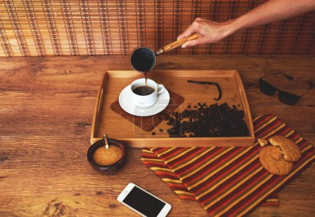 The girl pours coffee into a mug of pots, standing on a wooden circle spacing near a sugar bowl with brown sugar and round crispy biscuits