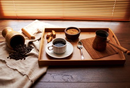 Breakfast is served on the balcony in front of a large curtained window, a cup of fresh coffee and biscuits, coffee beans that have been grinding and welded in cezve