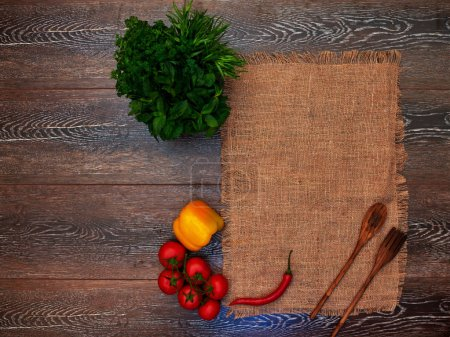 Photo for On the wooden table is for table linen cloth, a wooden spoon and fork, yellow peppers bunch of parsley and cherry tomatoes on a branch - Royalty Free Image