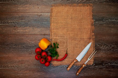 On the wooden table is for table linen cloth, a wooden spoon and fork, yellow peppers bunch of parsley and cherry tomatoes on a branch