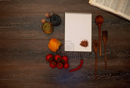 On a dark wooden table is a great cookbook notebook near where a housewife writes new recipes, ingredients laid out next to the sauce