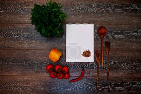 Photo pour Sur la table est un bloc-note, place votre annonce à côté des instruments en bois sont poivron jaune et rouge - image libre de droit