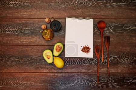 Cook writes in a notebook new recipes for a cookbook, avocado sauce with olive oil