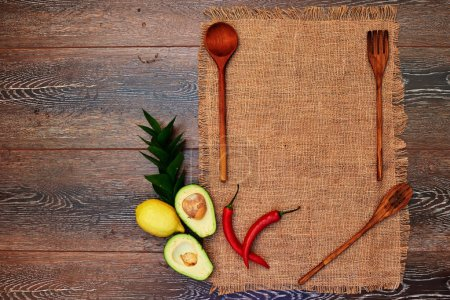 Photo for Ideas for the restaurant, dishes in a rustic style on lninoy on fabric with wooden instruments bright touch to the composition is hot peppers and avocado - Royalty Free Image