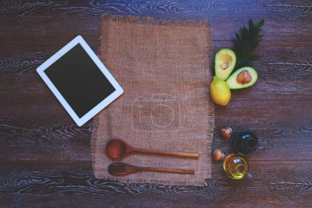 Photo for Home furnishings in the kitchen, handmade linen towel near modern tablet of last generation that next to a beautifully laid wooden cutlery and avocado salad for a light dressing of soy sauce - Royalty Free Image