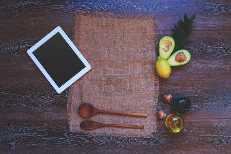 Foto de Muebles para el hogar en la cocina, toalla de lino hecha a mano cerca de moderno tablet de última generación junto a una cubertería de madera bellamente presentado y ensalada de aguacate para un aderezo ligero de salsa de soja - Imagen libre de derechos