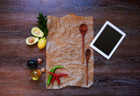 On a wooden table dark wood is  ipad air wooden cutlery two large spoons, decorated with composition of avocado and bright sharp red pepper