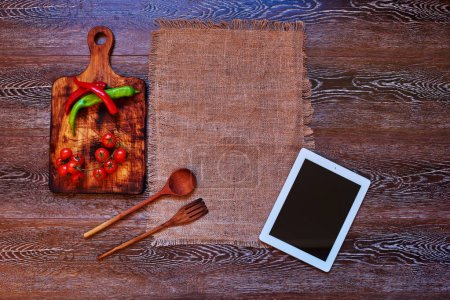 Photo for On the kitchen table restaurant chef left his plate and beige linen towel next to which is a wooden board for cutting vegetables and wooden cutlery, On the board is hot peppers and cherry tomatoes - Royalty Free Image