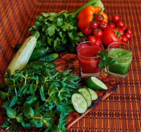 On the table is two cups with fresh juices in the first of tomato and pepper, rub a glass of cocktail in bright green with fresh cucumbers, zucchini and herbs and leek