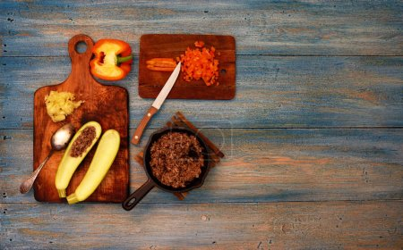 Photo for On the kitchen table housewife stuffed zucchini, ground beef, close cut pepper on salad - Royalty Free Image