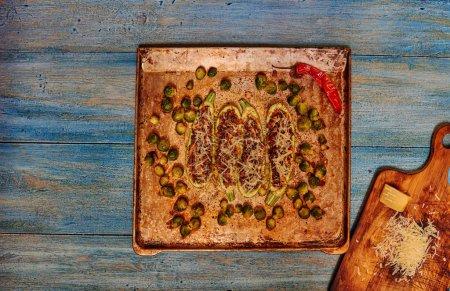 Photo pour Femme au foyer, posé sur une cuisson courgettes farcies à la viande hachée, frit dans une poêle jusque là, à côté de la courgette élargi des choux de Bruxelles comme garniture dans le plat - image libre de droit