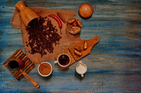 Morning coffee break served on the home kitchen, on the table, vintage blue crispy biscuits in the bank, the milk next randomly scattered grains of coffee in Cezve a fresh brewed coffee