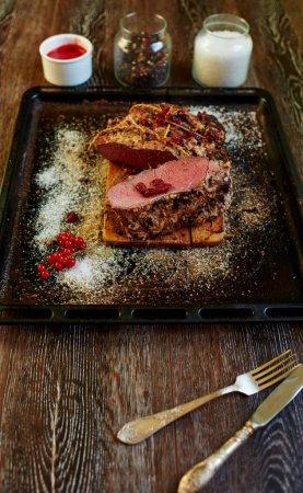 Photo pour Le chef de la tendance cher steakhouse préparé un morceau de filet de porc au four, la viande s'est avérée moyens rares endroits avec du sang pour les gourmets, la viande va cuire la sauce de fruits rouges - image libre de droit