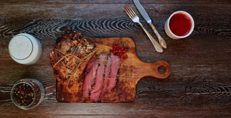 Cook bake in the oven a large piece of pork, well seasoned with spices and aromatic herbs, red meat, for gourmets, near steak are silver cutlery