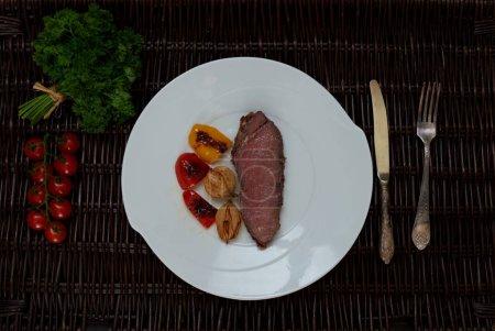 Photo pour Deux steak de veau grillé, déposer sur une plaque blanche, légumes pour la garniture - image libre de droit