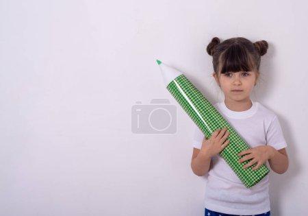 Kleines Mädchen mit Bleistift und Zeichnung oder Schreiben auf Wandkopierfläche