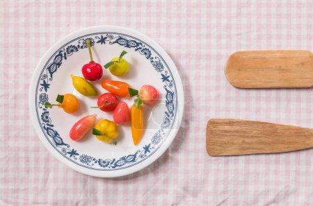 süßes Dessert in Fruchtform auf Teller mit kleinem Paddel auf rosa Serviettenhintergrund