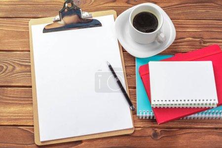Escritorio de oficina con bloc de notas con hojas en blanco, pluma y café