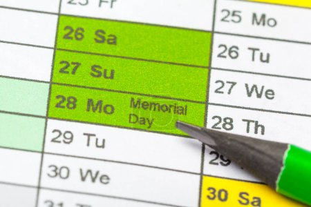Closeup of dates on calendar page and pencil