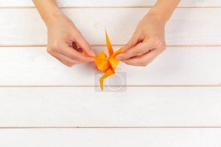Femme tenant l'oiseau en papier Origami sur fond en bois