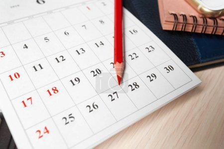 close up of calendar with red pencil