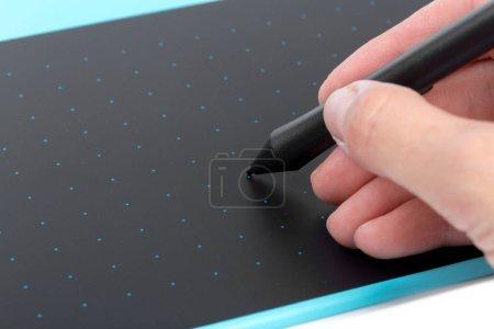 Designer hand using blue graphic tablet