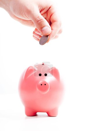 Savings concept, Piggy bank and hand with coin