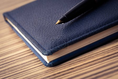 Pen on blue business notebook, close-up