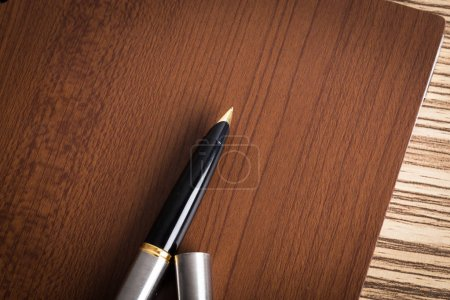 Pen on brown business notebook, close-up