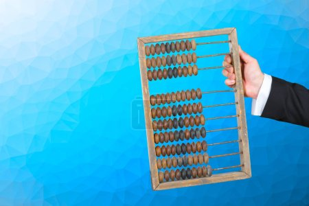 Businessman holding h abacus on blue, close up
