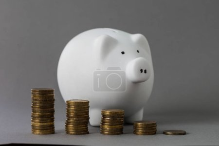 White piggy bank and coins on grey table