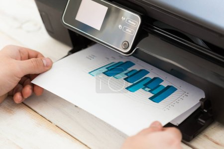 Man's hand making copies. Working with printer