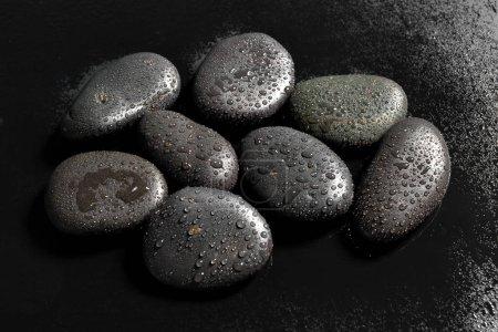 Massage stones on black background, close up
