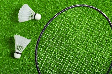 Shuttlecocks and badminton racket on green grass