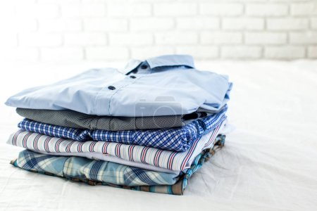 close up of ironed and folded shirts on table at home