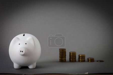 pink ceramic piggy bank and stacks of coins on grey background