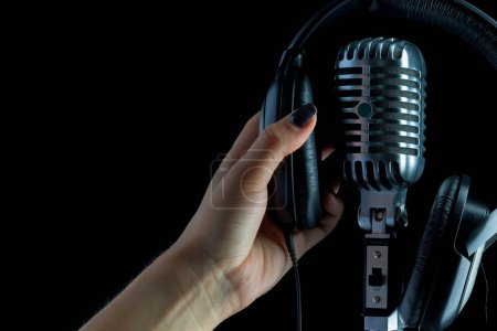 female hand on audio microphone in retro style