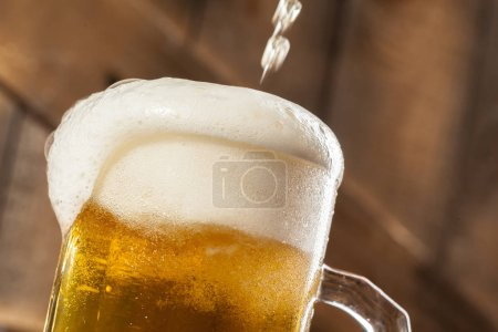 glass of beer with foam on wooden background