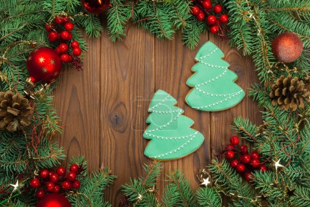 Christmas background with branch of fir tree decorated by gingerbread.