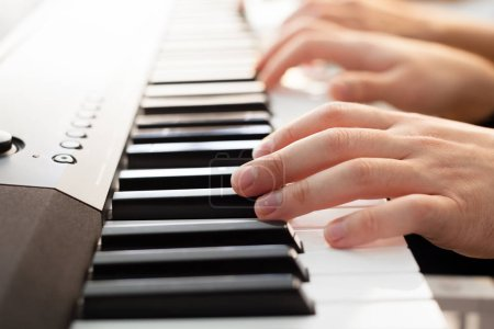 Closeup of hands playing piano, Music and hobby concept