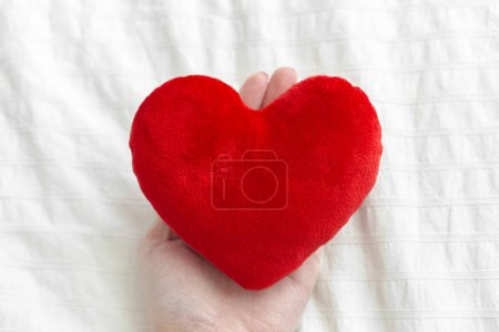 Red heart on hand over white textile  , valentine day concept
