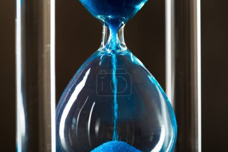 Time is passing. Blue hourglass close up