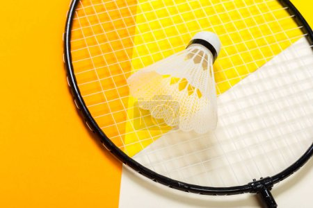 Shuttlecock and badminton racket on colorful background