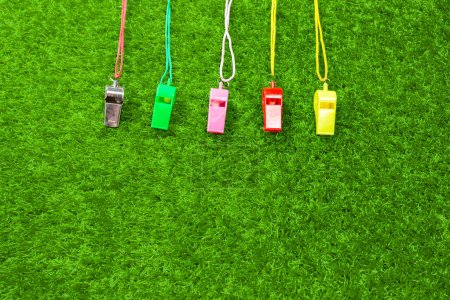 colorful Referee Whistles in row on green grass