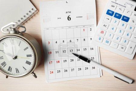 calendar, calculator, pen, note and clock on wooden background
