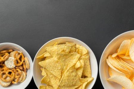 Salty snacks in bowls. Pretzels, chips, crackers