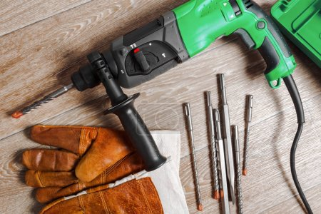 Electric hammer drill and work gloves laying on a wooden table