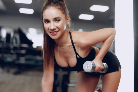Young brunette sporty woman exercising with dumbbe...